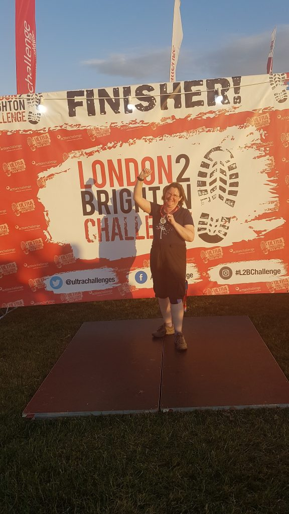 Me standing in front of a big Finisheer sign, holding my medal