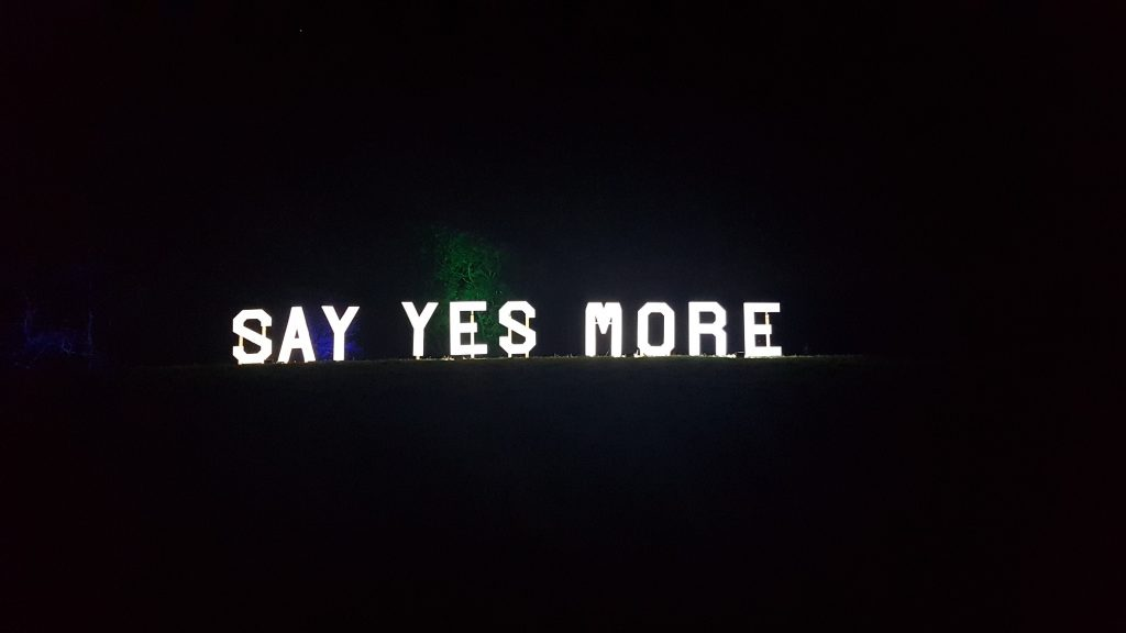 "A sign saying ""say yes more"", white lights against the darkness"