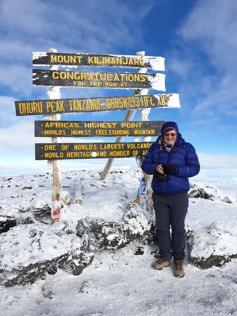 Me in front of sign at Uhuru point, summit of Kilmanjaro, heght 5895. Snow on ground and blue skies