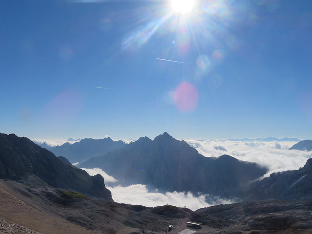 View from summit of Zugspitze. Blue skies and peaks of mountains sticking through clouds