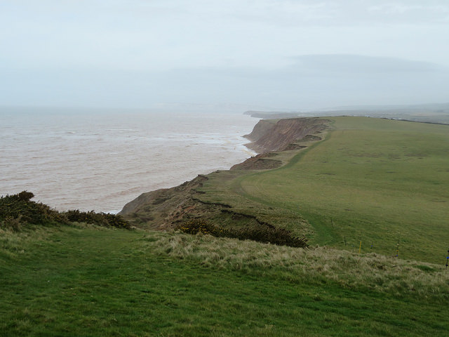 The cliffs on the South of the Isle of Wight Green hills, red stone cliffs. cloud over the sea