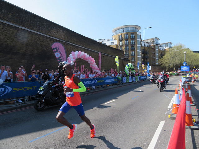 Mo Farah, in orange top and blue shorts, running the London marathon in April 2018