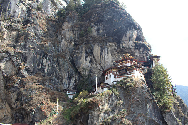 A red and white monastery on the side of a mountain in Bhutan