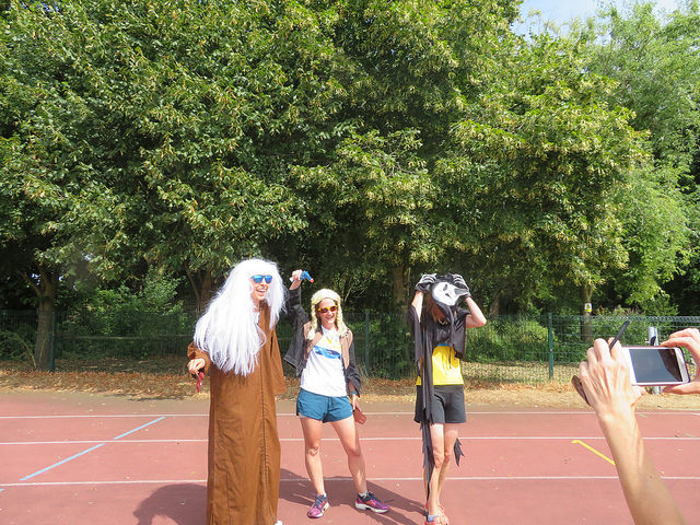 3 runners dressed in fancy dress standing on running track