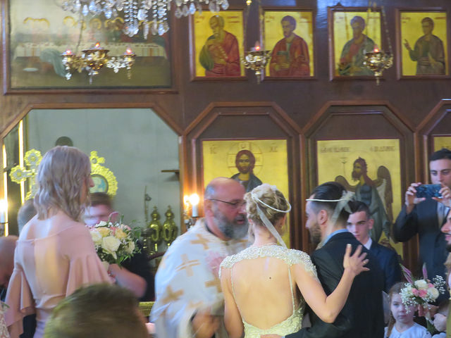 Bride and groom in front of priest. Behind alter are gold icons of saints