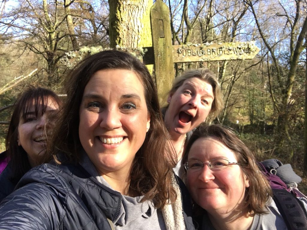 Four women grinning in the woods