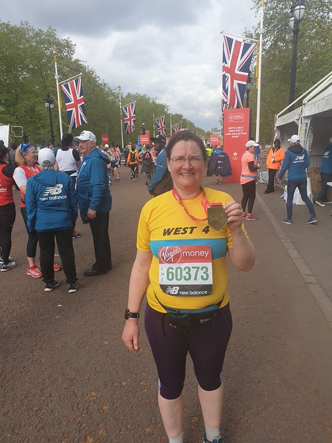 Holding up medal a tthe end of London Marathon