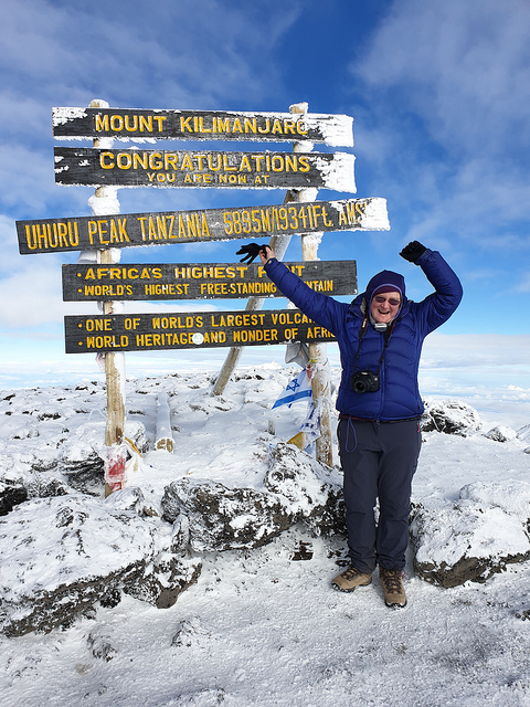 Me in front of the wooden sign on top of Kibo, the main summit of Kilimanjaro,, Snow on the ground