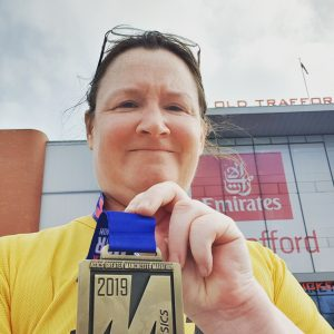 Me outside Old Trafford, holding up my Manchester Marathon medal