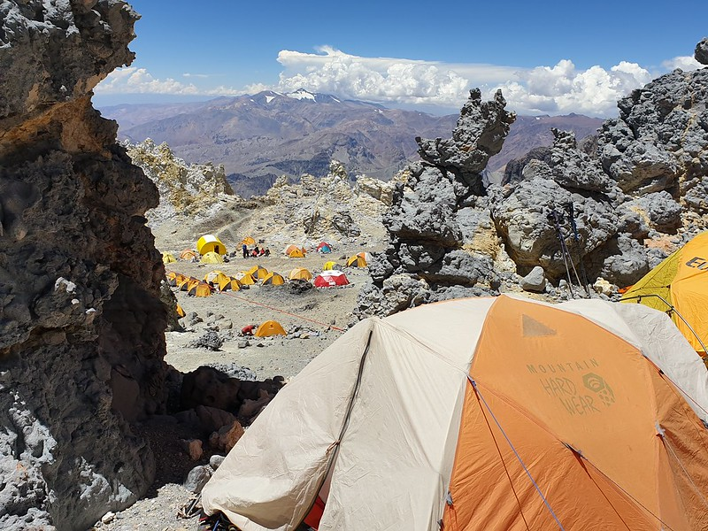 Orange and white tent set up at edge of cliff with more tents on plateau below. Mountains in the distance